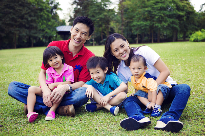 Happy Kao family sitting on the grass