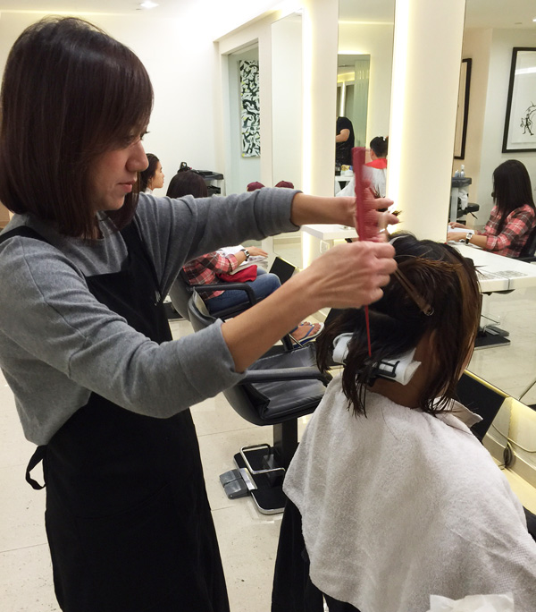 Annie applies a serum to protect my hair and scalp before the perm